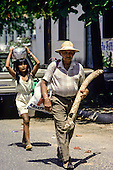 Boa Vista, Brazil. Man carrying a woven palm leaf manioc press with a Macuxi girl carrying a pot on her head.