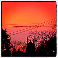 The morning glow rises in the east over the First United Methodist Church of Germantown, as seen from Cherokee Street in the Germantown section of Philadelphia, January 25, 2013.