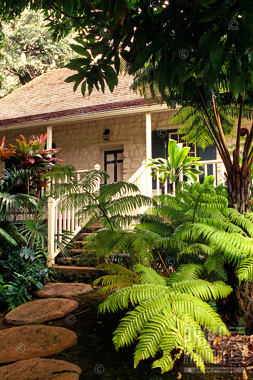 A view of a garden walkway toward an entrance on the grounds of Bailey House Museum, which is a converted historical mission house.  The museum features Hawaiiana and art and craft demonstrations.