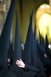 Row of hooded penitents entering Seville's cathedral during Holy Week, Spain