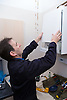 Gas man replacing the cover on to a boiler after fixing it,