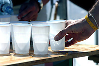 03 AUG 2003 - LONDON, UK - A competitor takes a cup of water from a drinks station at the London Triathlon. (PHOTO (C) NIGEL FARROW)