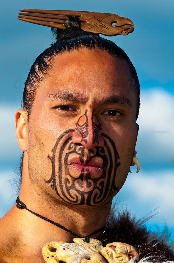 A Maori warrior with a ta moko (facial tattoo) performs a war haka (dance), Te Puia (New Zealand Maori Arts & Crafts Institute), Rotorua, New Zealand