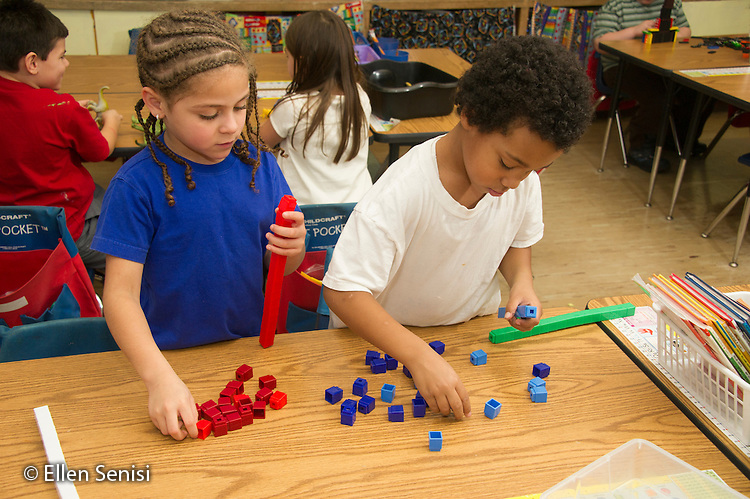 MR / Schenectady, New York. Yates Arts-in-Education Magnet School (urban public school). First grade classroom. Students play with interlocking blocks during their free play time. Left: Girl, 6, Hispanic American; Right: Boy, 6, bi-racial. MR: Car37, Gig1. ID: AM-g1w. © Ellen B. Senisi.