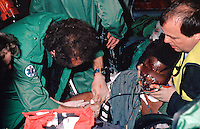 Paramedic, firefighters and police officers attend a RTA in which the driver remains trapped. The paramedic is attempting to find a vein in which to inject drugs. They have placed an oxygen mask and a neck brace on the victim. This image may only be used to portray the subject in a positive manner..©shoutpictures.com..john@shoutpictures.com