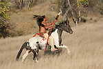 A Native American Indian man riding bareback on a horse in the prairie of South Dakota