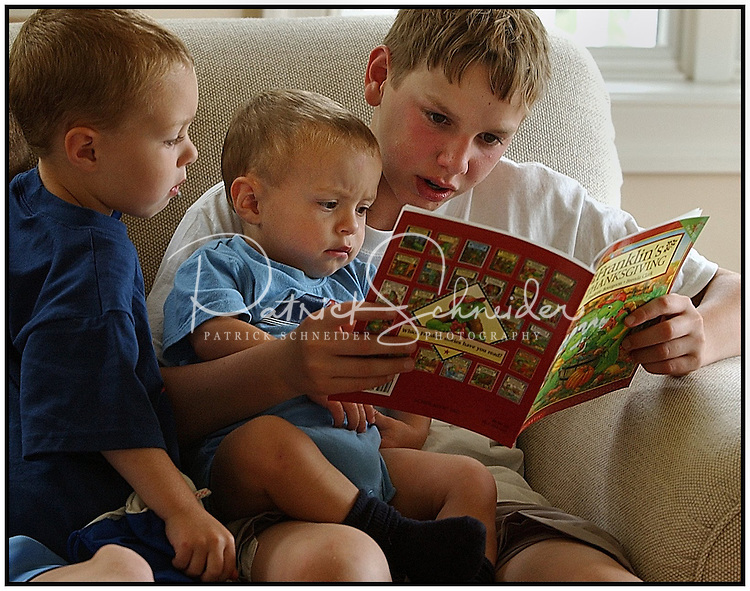 An older boy reads to two younger boys. Model released image may be used to illustrate other destinations or concepts.