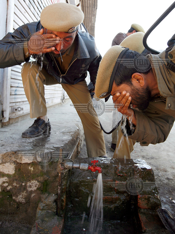 Paramilitary police rinse their eyes after being exposed to tear gas during clashes with stone throwing youth clash following Friday prayer at the Jamia Masjid mosque.  Srinagar, Kashmir, India.  Fredrik Naumann/Felix Features