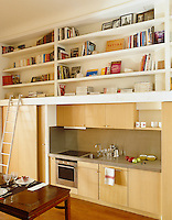 Built-in book shelves benefit from the double-height luxury of this kitchen/dining room