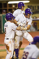 LSU Tigers second baseman Jared Foster (17) is hugged by teammates Alex Bregman (8) and Mark Laird (9) following their walk-off win in the Southeastern Conference baseball game against the Texas A&M Aggies on April 23, 2015 at Alex Box Stadium in Baton Rouge, Louisiana. LSU defeated Texas A&M 4-3. (Andrew Woolley/Four Seam Images)