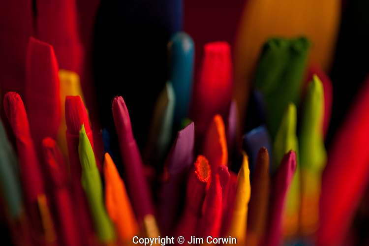 Multicolored paint brushes in a paint can covered with paint drips