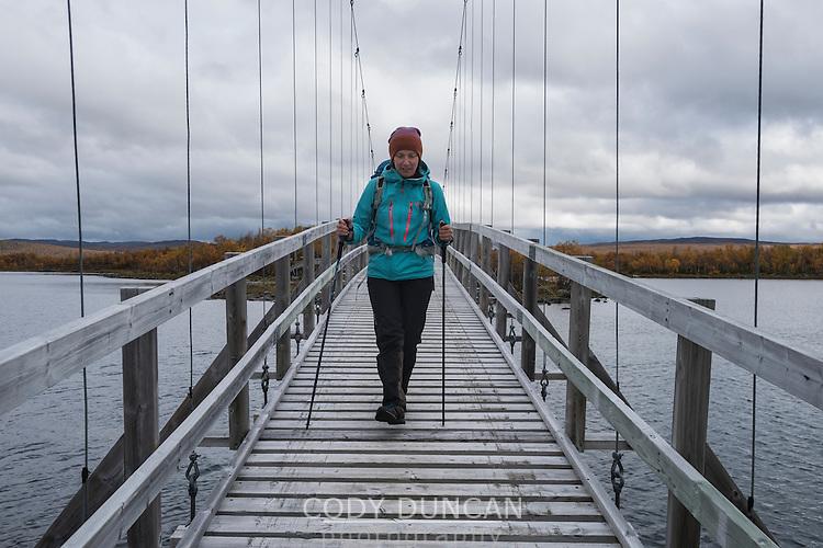 Female hiker crosses bridge between islands on lake Tärnasjön, Kungsleden trail, Lapland, Sweden