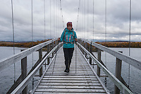 Female hiker crosses bridge between islands on lake Tärnasjön, Kungsleden trail, Lapland, Sweden
