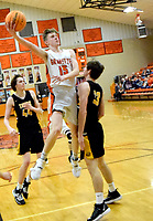 Westside Eagle Observer/MIKE ECKELS<br /> <br /> Sandwiched between two Tiger defenders, Alex Edmiston (33) and Jake Webb (44), Tristan Batie (Lions 15) attempts a hook shot during the Gravette-Prairie Grove home conference contest Jan. 14. Batie's shot missed but was rebounded by a team mate whose shot hit its mark for a field goal.