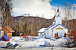 Russian Orthodox Church viewed through Spirit Houses, Eklutna Cemetary, Eklutna Village Historical Park, Southcentral Alaska, Winter.