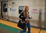 Merrick, New York, U.S. - July 14, 2014 - During evening rush hour, young woman who got off train wears cell phone earbuds as she runs on elevated platform of Merrick train station of Babylon branch, after MTA Metropolitan Transit Authority and Long Island Rail Road union talks deadlock, with potential LIRR strike looming just days ahead.