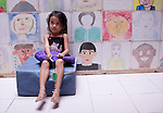 A girl waits before her eye exam  at the children and family waiting area at the Angkor Children's Hospital in Siem Reap, Cambodia.