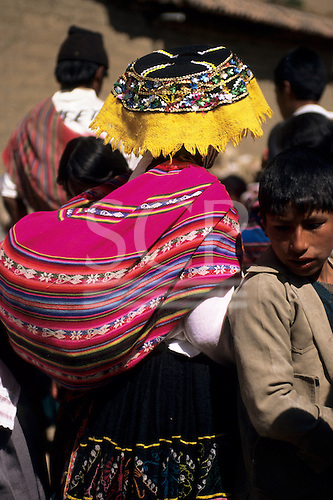 Paucartambo, Peru. Woman wearing traditional dress and carrying a baby in a manta on her back.