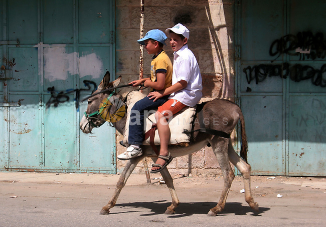 Children of Israeli settlers enjoy a donkey ride in a closed Palestinian street, where only Jewish settlers are allowed, inside the old city of the West Bank town of Hebron on September 26, 2010. A large group of right-wing Jews toured the area with Israeli soldiers escort on the day when the government's settlement freeze is due to expire. Thousands of right-wing Jews are expected in a West Bank settlement later today to begin building. Photo by Mamoun Wazwaz