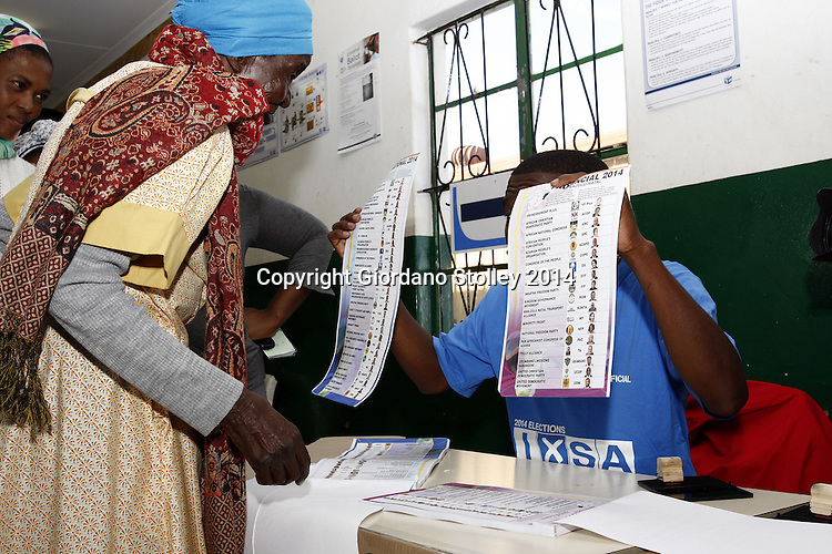 NKANDLA - 7 May 2014 - An election official at Ntolwane Primary School in the Nkandla areal explains to 81-year old Hlaleleni Zulu that she has two votes -- one national and one provincial. Picture: Allied Picture Press/APP
