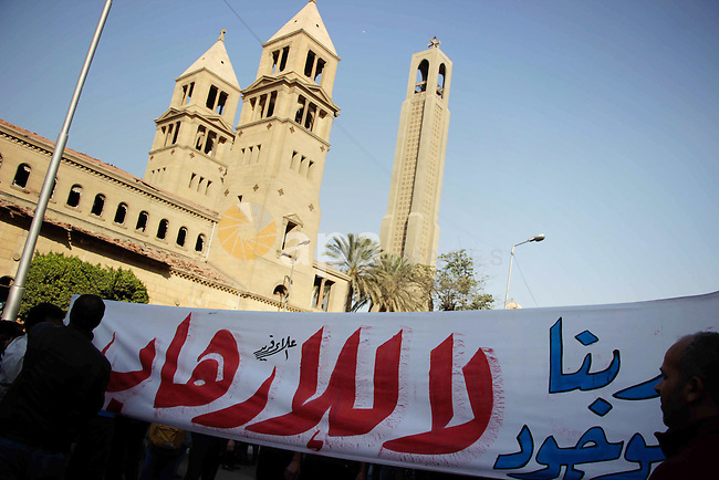 Egyptian Christians chant anti-terrorism slogans outside the the Saint Peter and Saint Paul Coptic Orthodox Church in Cairo's Abbasiya neighbourhood after it was targeted by a bomb explosion on December 11, 2016, . The blast killed at least 25 worshippers during Sunday mass inside the Cairo church near the seat of the Coptic pope who heads Egypt's Christian minority, state media said. Photo by Amr Sayed
