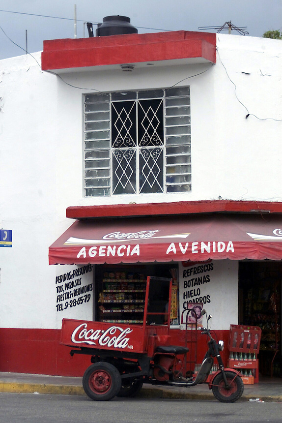 Red and white storefront with motorized cart in Merida, Mexico.