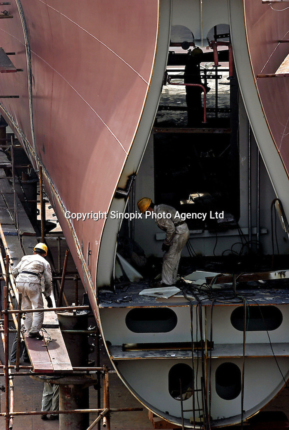Chinese workers operating on the tail section of a ship under construction at the Hudong Zhonghua Shipbuilding Co., LTD in Shanghai, China. China is the world's third largest shipbuilding nation after South Korea and Japan. While growing international interest in its lower building cost and domestic tanker demand to fulfill the country's hunger for energy is likely to push the country to the top position, the rapidly increasing price of steel has also undercut the industry's profitability..