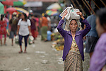 A woman carries a bag on her head through the Tahan Market in Kalay, a town in Myanmar. This market is located in Tahan, the largely ethnic Chin section of the town.