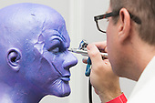 London, UK. 12 April 2015. Makeup Artist Chad Washam from Make-up designory airbrushes makeup to a female version of the Avengers' villain Thanos. United Makeup Artists Expo (UMAe),  the UK's leading aspiring and professional hair and makeup artist trade show, at the Business Design Centre in Islington, London, UK. It runs until Sunday, 12 April. At this trade show leading professionals provide demonstrations and the latest techniques and products are showcased.