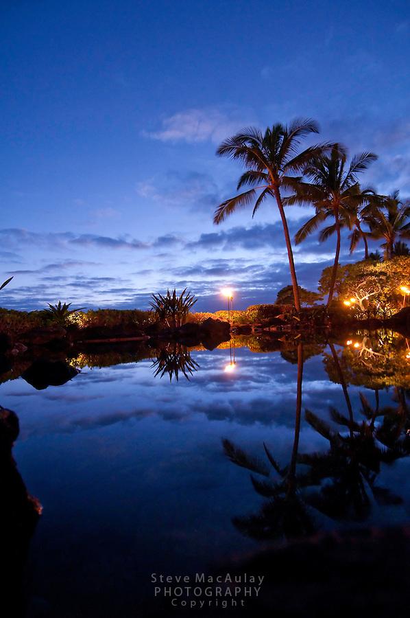 Twilight view of pool with palm trees reflected at Grand Hyatt Kauai Resort, Kauai, Hawaii