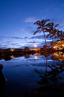 Twilight view of pool with palm trees reflected at Grand Hyatt Kauai Resort, Kauai, Hawaii