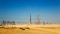 Dubai.  Skyline of the Downtown Dubai Development with the Burj Dubai, Business Bay and Financial Centre.  Electricity transmission lines and pylon..