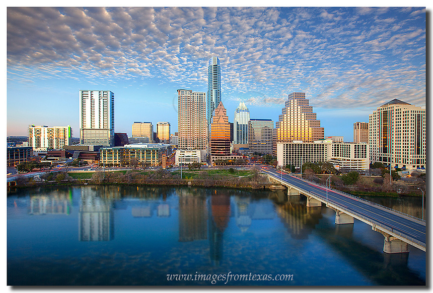 On a mild, January evening, late afternoon clouds roll over the city in this Austin skyline image. This view of downtown Austin was captured from the Hyatt and looks out over Ladybird Lake. In the distance, the Austin icons - the Frost Bank Tower and the Austonian, rise into the puddled blue sky.