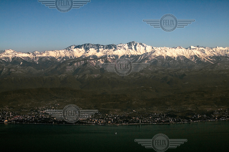 The resort city of Sochi, which lies along the Black Sea coast at the foot of snow-peaked mountains.