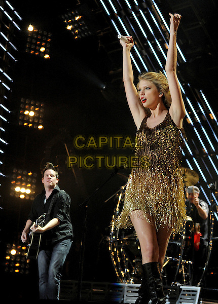 Taylor Swift.2011 CMA Music Festival Nightly Concert held at LP Field, Nashville, Tennessee, USA..June 12th, 2011.stage concert live gig performance music half length gold dress tassels fringed dress hand arms in air 3/4 full boots black.CAP/ADM/LF.©Laura Farr/AdMedia/Capital Pictures.