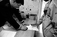 Roma 2000.Carcere di Regina Coeli  .Ufficio Matricola, agente della Polizia Penitenziaria prende le impronte ad un nuovo detenuto. Regina Coeli (Queen of Heaven) Prison.Office Matriculates, Police officer Penetentiary  took  fingerprints to a new prisoner