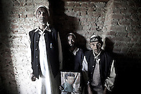 Gulan Hassan (first left) and two of his remaining three brothers (right) appear in the list of families that have suffered the disappearance of a loved one by Indian forces. They show Abdullah Hassan's portrait, their 22-years-old brother when disappeared. Abdullah is one name among those 8,000 enforced disappeared persons in the last 20 years of conflict. Baramulla district, Indian administrated Kashmir.