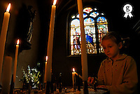 Girl (5-7) lighting candle in church, low angle view (Licence this image exclusively with Getty: http://www.gettyimages.com/detail/200476770-001 )