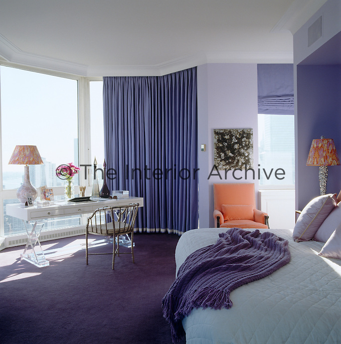 The master bedroom is decorated in restful tones of deep violet and has stunning views of the city from floor-to-ceiling windows