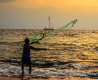 Fine Art Photo of net fishing during a beautiful evening sunset on Banderas Bay, Puerto Vallarta, Mexico. Beautiful scene of the fisherman casting his net as a sail boat goes by.