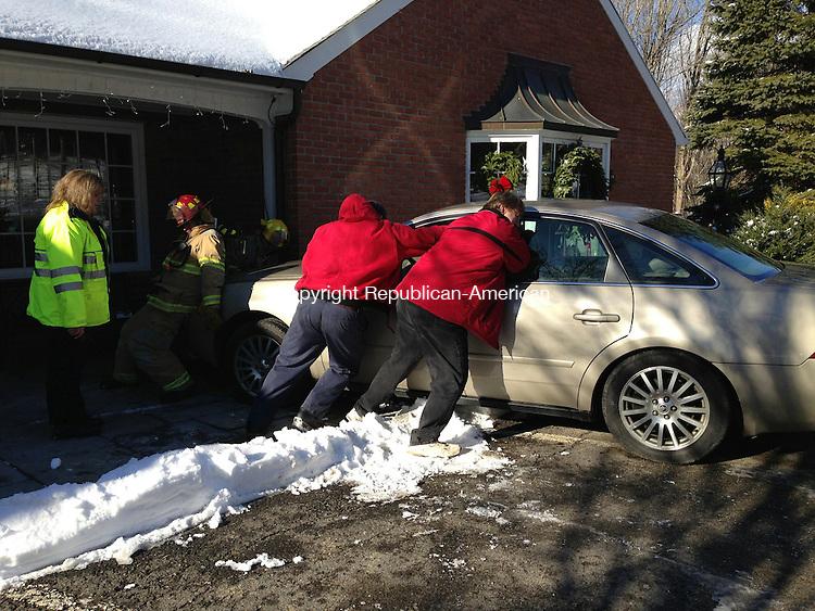 WOODBURY, CT - 16 Dec 2013 - 121613RH01 - Firefighters  push a car away from Woodbury Pewter on Main Street South in Woodbury, where a driver had crashed into the brick front of the building. Rick Harrison Republican-American
