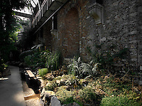 Plant History Glasshouse (formerly Australian Glasshouse), 1830s, Rohault de Fleury, Jardin des Plantes, Museum National d'Histoire Naturelle, Paris, France. An atmospheric low angle view of a stone wall leading to the arch of the metal and glass structure, in the afternoon light and shade.