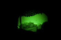 US soldiers from 1st platoon Alfa company, 3-103d armor regiment, 28th US National Guard Division see Ramadi through their night vision nods while on a three day rotation on OP ( observation post) HOTEL, a five floors building in Western Ramadi, capital of the Anbar province, Iraq on the day of the national electionsTHURS DEC 15th 2005..Nor US military or Iraqi Army  were in charge of securing the Ramadi polling stations during the elections. they simply conducted daily routine patrols hoping that the insurgency would keep its promise not to attack on this day. US forces watched the voting form observation posts located at the boarder of the city. OP HOTEL is one of them on code name route MICHIGAN. On August 15 2005 a suicide bomber detonated a truck filled with more than 500 KGs of explosives in front of the main entrance. Due to heavy fortification no US soldiers suffered deadly wounds. The OP scans a strip of road on which more than 60 improvvised explosive devices are found or detonated every month. life at the HOTEL is quite simple. US squads rotate on the numerous observation posts in the building every six hours for three hours. sniper teams keep the area constantly in their rifle scopes. it's a 24 hour, non stop process. hot meals are driven by platoon members once a day. living conditions are miserable. the worst part of it all is being trapped in a fortified buliding, where the only windows available are the ones out of which they  shoot all their weapons. these soldiers saw the elections through these holes, with their body armors and their night vision nodes, through their rifle scopes and with the constant soundtrack of bombs, mortars and small arms fire always present in the background.