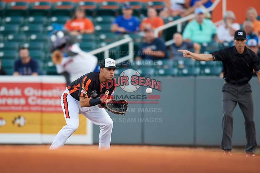 Aberdeen IronBirds first baseman J.C. Escarra (13) fields a ground ball as first base umpire Jae-Young Kim points to indicate that the ball is fair during a game against the Staten Island Yankees on August 23, 2018 at Leidos Field at Ripken Stadium in Aberdeen, Maryland.  Aberdeen defeated Staten Island 6-2.  (Mike Janes/Four Seam Images)