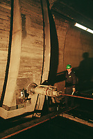 Switzerland. Canton Lucerne. A man with a green helmet controls the armor plate door's closure in the Sonnenberg tunnel in Lucerne during the largest civil defense exercise ever held in the country. A hydraulic cylinder (also called a linear hydraulic motor) is a mechanical actuator that is used to give a unidirectional force through a unidirectional stroke. From 16 to 21 November 1987, almost 1200 men and women converted a motorway tunnel into perhaps the world's largest bunker structure. The civil protectors had to prove during the exercise «Ameise» ( Ants in english) that in an emergency more than 20,000 inhabitants of the city of Lucerne could survive here in the mountain for two weeks. The Sonnenberg Tunnel is a 1,550m  long motorway tunnel, constructed between 1971 and 1976. At its completion it was also the world's largest civilian nuclear fallout shelter, designed to protect 20,000 civilians in the eventuality of war or disaster. Based on a federal law from 1963, Switzerland aims to provide nuclear fallout shelters for the entire population of the country. The construction of a new tunnel near an urban centre was seen as an opportunity to provide shelter space for a large number of people at the same time. The giant bunker was built between 1970 and 1976 at a cost of 40 million Swiss francs. The shelter consisted of the two motorway tunnels (one per direction of travel), each capable of holding 10,000 people in 64 person subdivisions. A seven story cavern between the tunnels contained shelter infrastructure including a command post, an emergency hospital, a radio studio, a telephone centre, prison cells and ventilation machines. The shelter was designed to withstand the blast from a 1 megaton nuclear explosion 1 kilometer away. The blast doors at the tunnel portals are 1.5 meters thick and weigh 350 tons. The logistical problems of maintaining a population of 20,000 in close confines were not thoroughly explored, and testing the installation was diff