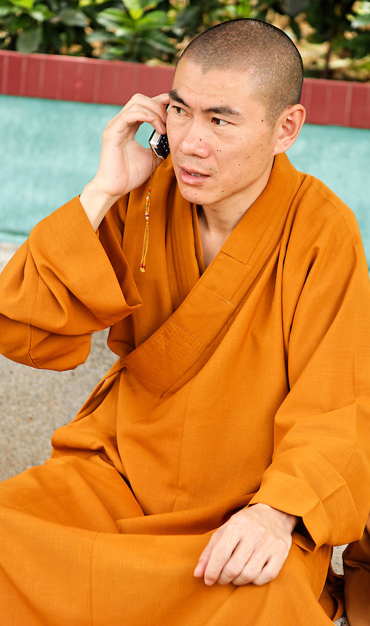 Buddhist monk on cell phone at Po Fook Hill Cemetery, Sha Tin, New Territories, Hong Kong SAR, People's Republic of China, Asia