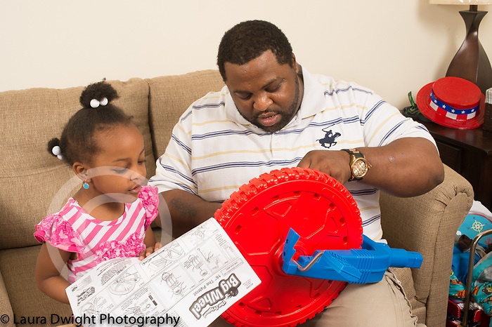 4 year old girl at home with father holding pictorial directions and talking as he assembles plastic tricycle