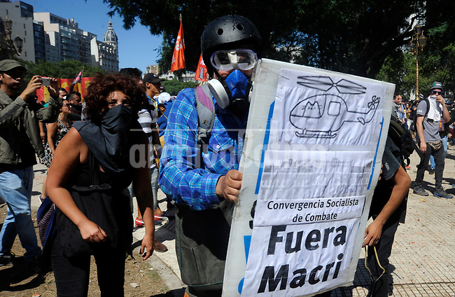 A rioter shows a graffiti against president Mauricio Macri during severe clashes   near the Congress building while Deputies Chamber was   discussing changes in   retirement legislation