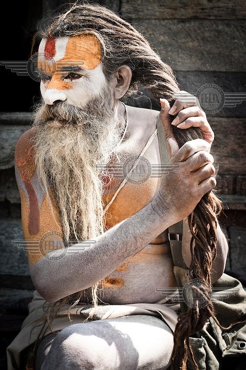 An Hindu sadhu twists his dreadlocks while sitting outside the The Pashupatinath Temple.