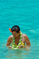 Woman surrounded in blue ocean looking at orchid flower lei